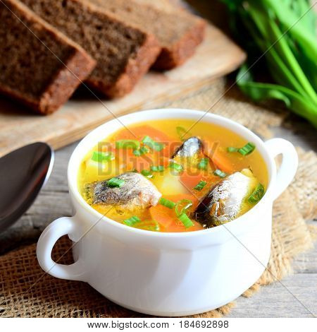 Light fish soup recipe. Delicious fish soup with potatoes, carrots and green onions in a bowl. Rye bread pieces, spoon on rustic wooden table. Closeup