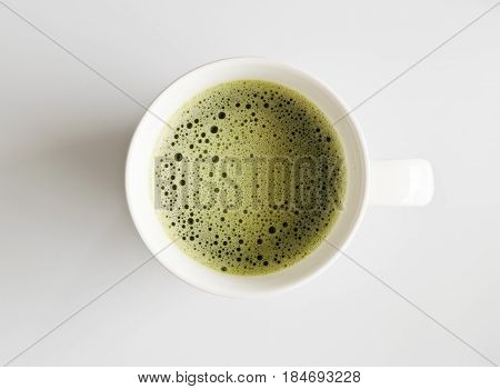 Cup of green matcha tea on white background, top view.