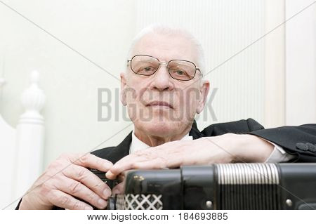 Senior musician posing with harmonica indoor cropped portrait