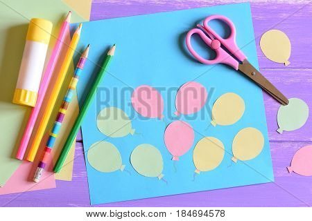 Card with paper air balloons, scissors, glue stick, colored paper, pencils on a table. Teaching kids to use scissors, glue stick and pencils. Fun and easy preschool and kindergarten paper crafts