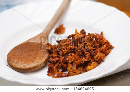 fried lard cracklings on a white dish with a wooden spoon