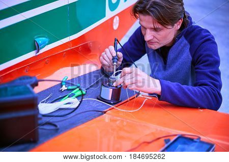 The electrician performs the soldering of wires with a soldering iron.
