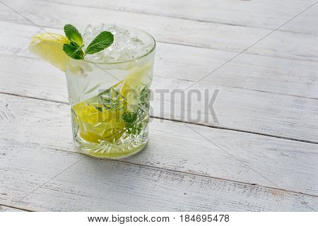 Cocktail with lime , ice and peppermint on white wooden background .