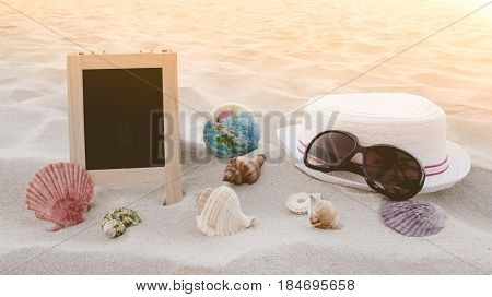 Straw Hat, Sun Glasses, World Ball Toy, Seashell And Blank Blackboard For Text On Clean Sand Beach.