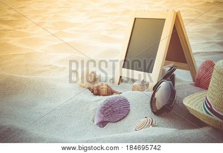 Straw Hat, Sun Glasses, Yellow Ball, Seashell And Blank Blackboard For Text On Clean Sand Beach. Bea