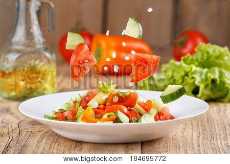 Summer Light Air Salad Of Fresh Vegetables On A Wooden Background. Levitating Salad Ingredients. Sti