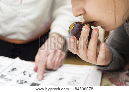 A little girl eating a fruit and listening a teacher pointing a finger in a book Selective focus cropped shot