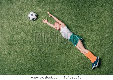 Top View Of Little Boy Pretending Playing Soccer On Grass, Athletics Children Concept