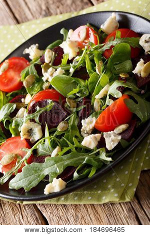 Salad With Beets, Arugula, Tomatoes, Roquefort Cheese And Pumpkin Seeds Close-up. Vertical