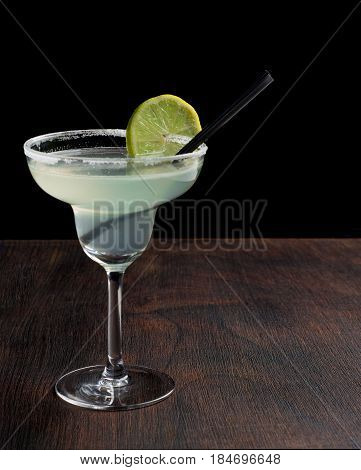 margarita cocktail with lime on dark background.