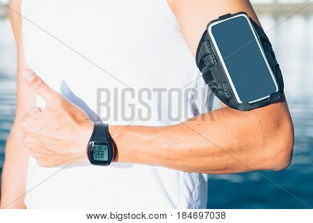 Man with armband and pulse meter showing thumb up gesture.