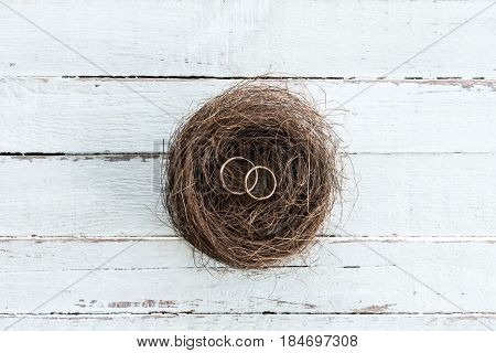Top View Of Golden Wedding Rings In Decorative Nest On Wooden Tabletop, Wedding Rings Background