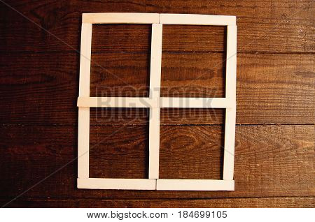 Wooden sticks lie on a wooden background ornament in the form of a window