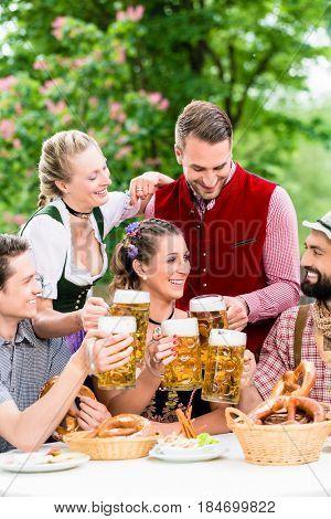 In Beer garden - friends in Tracht, Dirndl and Lederhosen drinking a fresh beer in Bavaria, Munich, Germany