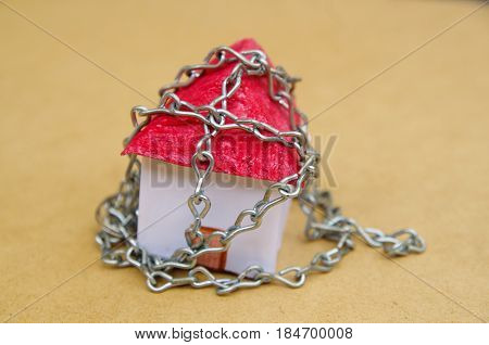 Chain wrapped around a beautiful an small model house made of paper.