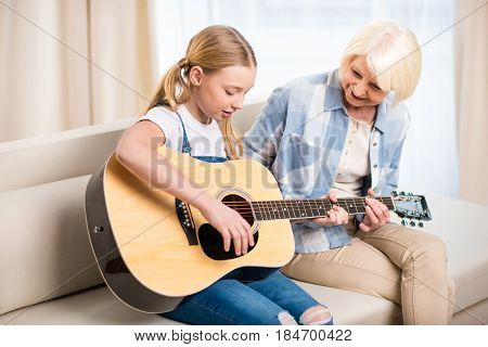 Smiling Senior Woman Looking At Preteen Girl Playing Acoustic Guitar On Sofa