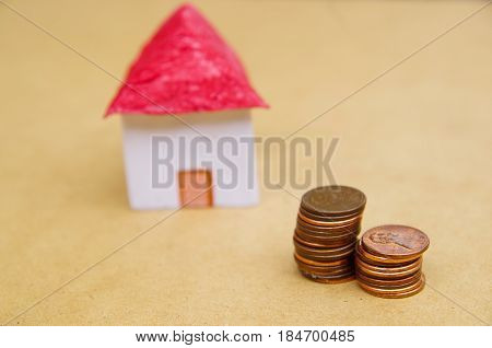 Small beautiful house with coins stacked in front of the housing model pretending: house prices, house buying, real estate, mortgage concept.