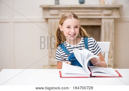 Cute Preteen Girl Sitting At Table With Book And Smiling At Camera