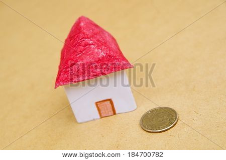 Small beautiful house with a coin in front of the housing model pretending: house prices, house buying, real estate, mortgage concept.