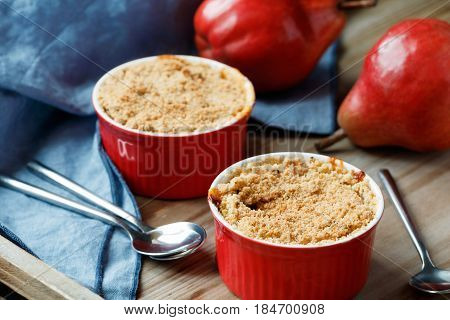 Close-up of a portion desserts pear crumble pie in a red bowl on a wooden table.