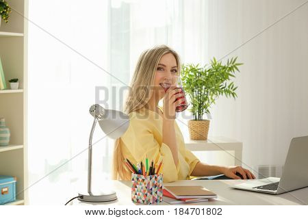Beautiful young woman drinking fresh juice at home