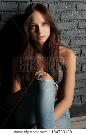 Young brunette in crop top and ripped jeans sitting on the floor leaning against the brick wall. Vertical photo