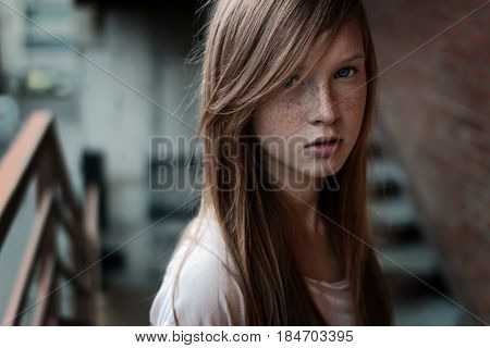 Close-up portrait of a redhead girl with freckles and blue eyes standing on the stairs and looking at camera. Horizontal photo