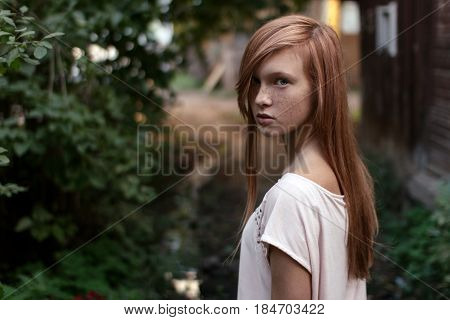Portrait of a redhead girl with freckles and blue eyes standing in half-turn in the green garden flooking at camera. Horizontal photo