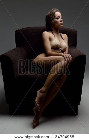 beautiful graceful and slender girl in a beige bra sitting in a chair with closed eyes