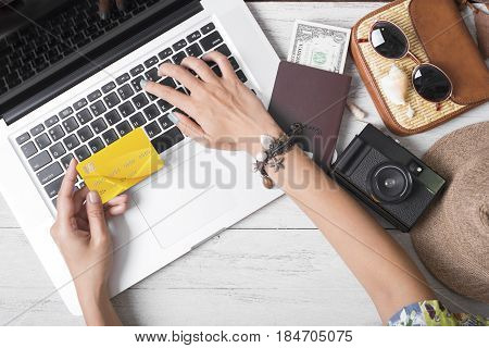 Summer holiday hand people holding credit card online booking traveling on Laptop among white wooden background.