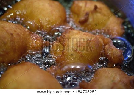 Donuts frying in hot oil. Horizontal image.