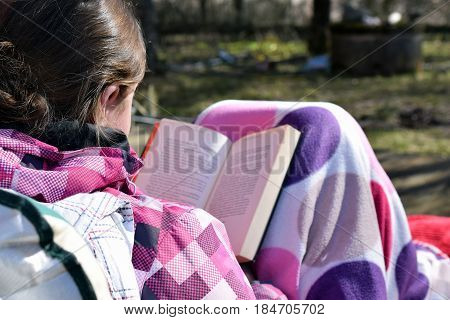 Young woman sitting outdoors, covered with blanket and reading a book on beautiful spring day.