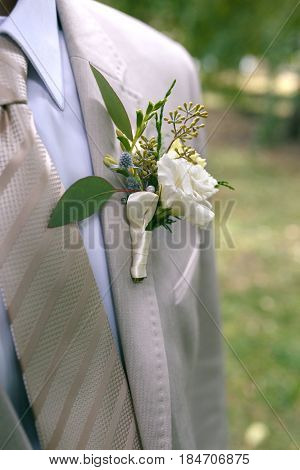 Boutonniere of white and yellow flowers with greens on lapel of a gray jacket. Close-up photo