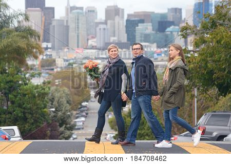 Happy family holding hands crossing the street in San Francisco, talking and smiling, city skyline behind them.