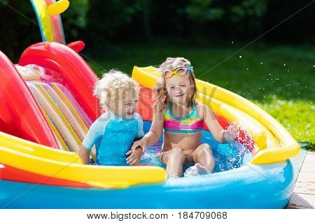 Kids In Garden Swimming Pool With Slide