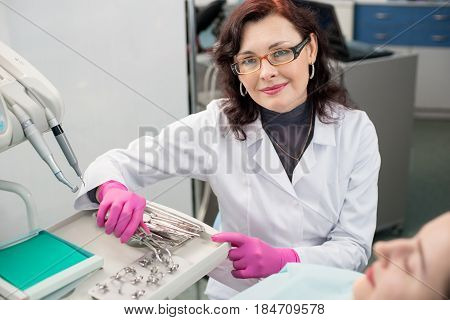 Portrait Of Friendly Female Dentist With Female Patient In The Dental Office. Doctor Wearing Glasses