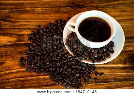 Americano coffee in white cup on wood background.