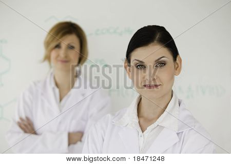 Two Cute Women In Front Of A White Board
