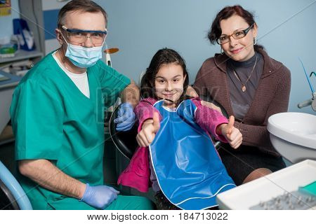 Portrait Of Senior Pediatric Dentist And Girl With Her Mother On The First Dental Visit At The Denta