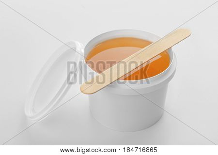 Plastic bucket with sugaring paste and stick on white background