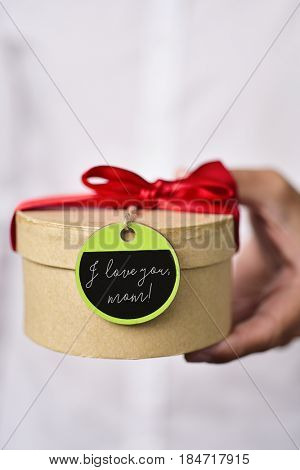 closeup of a young caucasian man in a white shirt holding a gift box tied with a red ribbon and with a green and black label tied to it with the text I love you, mom written in it