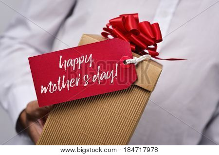 closeup of a young caucasian man in a white shirt holding a gift box with a red label tied to it with the text happy mothers day written in it