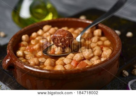 closeup of an earthenware bowl with potaje de garbanzos, a spanish chickpeas stew with chorizo and serrano ham, on a rustic wooden table