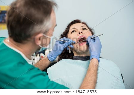 Woman Having Dental Check Up In Dental Office. Dentist Examining A Patient's Teeth With Dental Tools