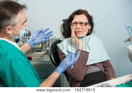 Woman Feeling Toothache, Touching Cheek With Hand At Dental Clinic. Senior Dentist Trying To Help. D