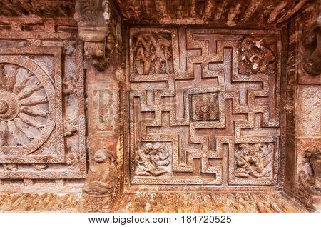 Background of Indian rock-cut architecture. Ceiling with carved maze with sun symbols. 6th century cave temple in town Badami, India.