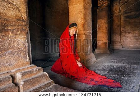 Lady in red dress thinking about life on the floor of ancient cave temple in Karnataka, India.