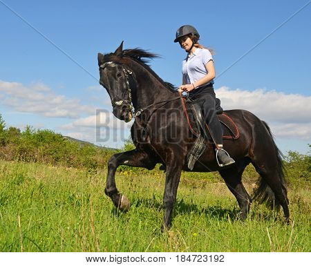 young riding girl and her black stallion in nature