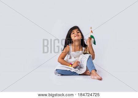 cute little indian girl holding indian flag or tricolour over white background