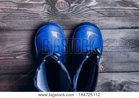 Blue Rubber boots for rainy day on wooden background. Autumn kids boots concept